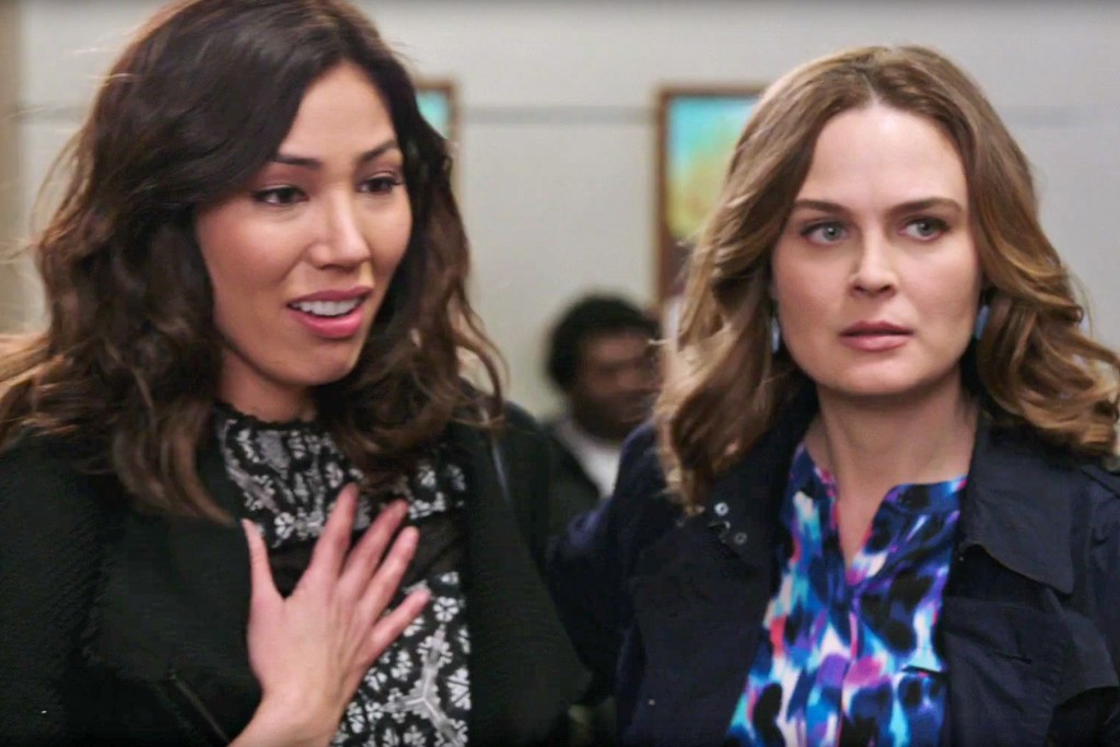 Image: Angela Montenegro clutches her heart while standing next to Bones, played by Emily Deschanel. Both women are wearing patterned shirts and blazers.