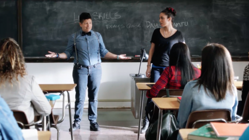 Image: Daisy Cantu, a butch latinx person, stands in front of a classroom of teenage students in a bowtie, denim shirt, suspenders and jeans.