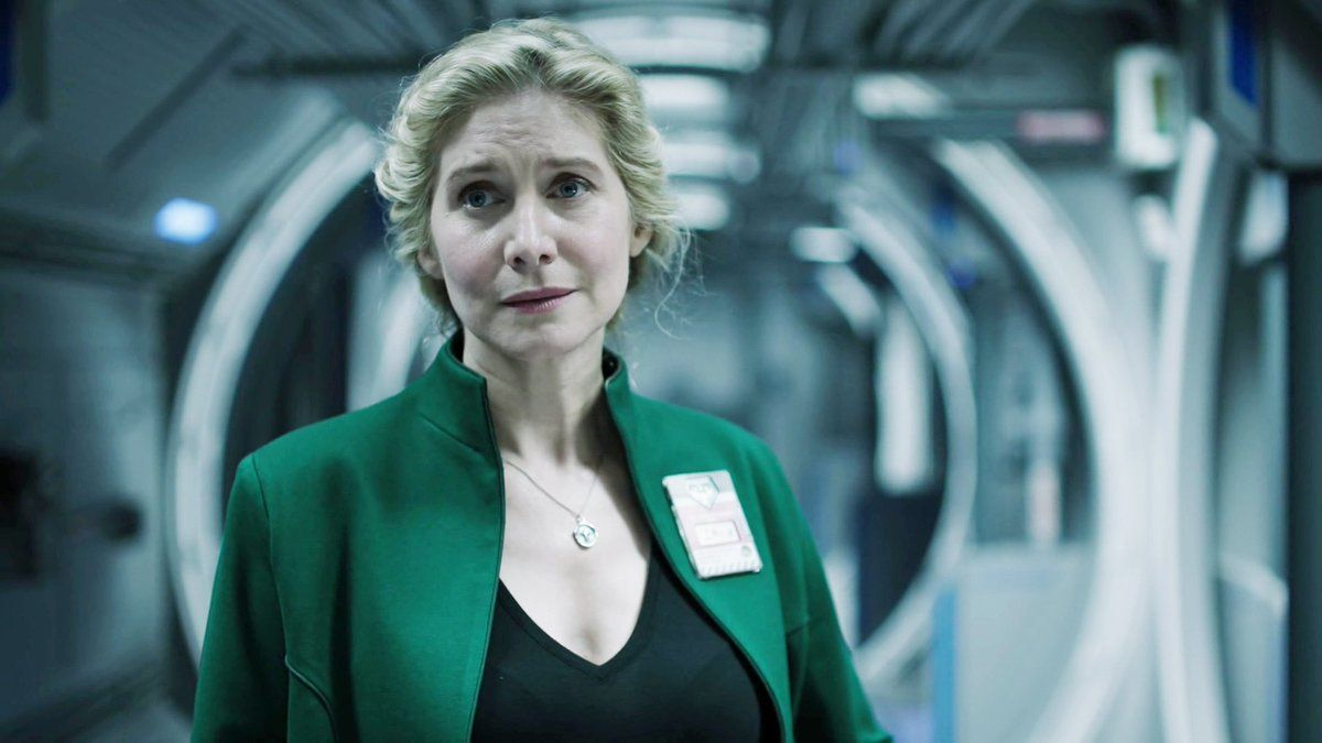 Image: a middle-aged white woman in a black v-neck shirt and green blazer stands in what appears to be the hallway of a spaceship. She looks concerned.