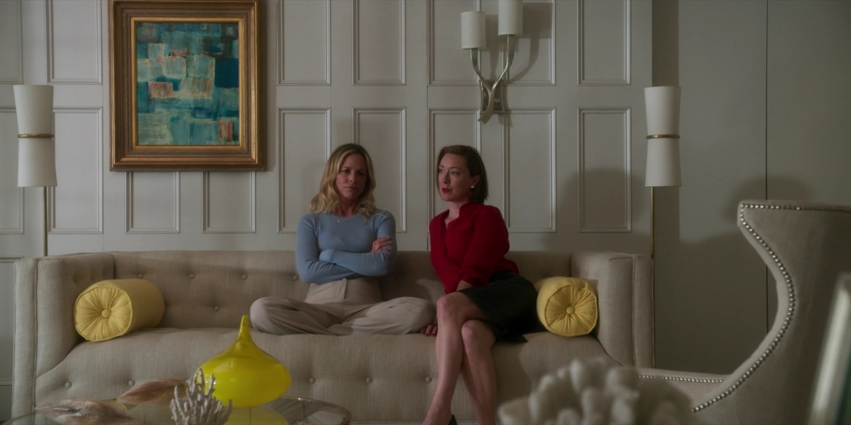 Image: A living room that exudes an air of wealth. White walls, off-whtie sofa, white lighting fixtures, some yellow accents, a gold-framed photo. On the sofa sit two white women. One is wearing a skirt her legs, bare from the knees, are crossed with her feet on the floor, and is leaning slightly towards the other, who is relaxed and sitting cross-legged on the couch in a blue sweater. She is looking at the camera.
