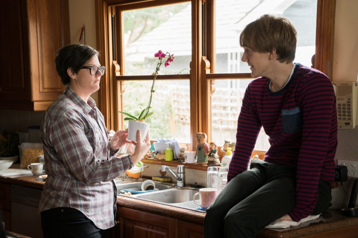 Image: a butch lesbian in plaid holds a little flower pot over the sink, a white boy in a striped shirt sits on the counter. The lesbian seems confused.