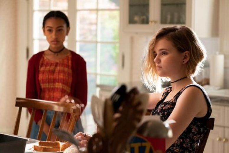 Image: Izzy, a young white teenage girl in a choker and sleeveless dress and an undercut, is sitting in her family kitchen. Ruby, a Black girl in a cardigan, is standing behind her. They are both looking at the same thing but not each other.