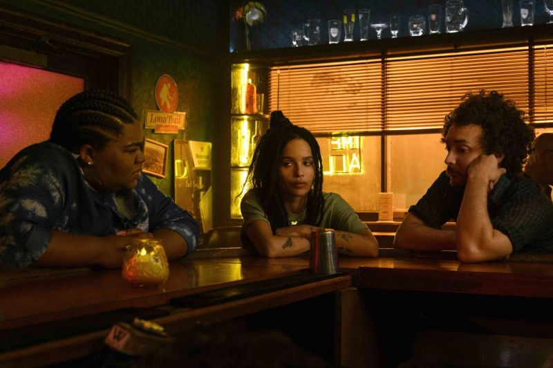 Image: Rob, played by zoe Kravitz, looks a little unreadable, her friends are sitting on either side of her in a dark bar, looking confused.