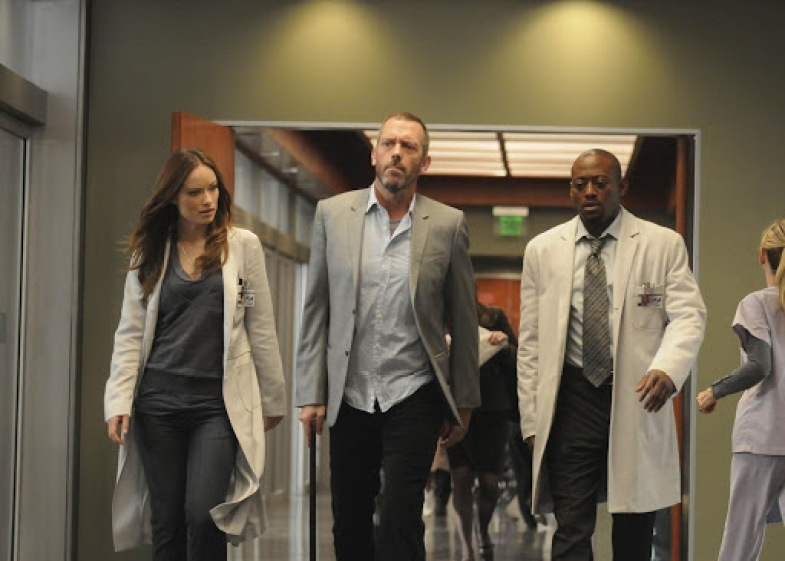 Image: the hallway of a hospital. Three people walking down the hallway. In the middle is Dr. House, tall white and thin in a blazer and button-up shirt. to his right is Thirteen, played by Olivia Wilde, in dark blue scrubs and a white doctors' coat. To his left is Dr. Eric Foreman, played by Omar Epps. Foreman is Black and wearing a shirt and tie and a white doctors coat. They seem to be in a mild hurry.