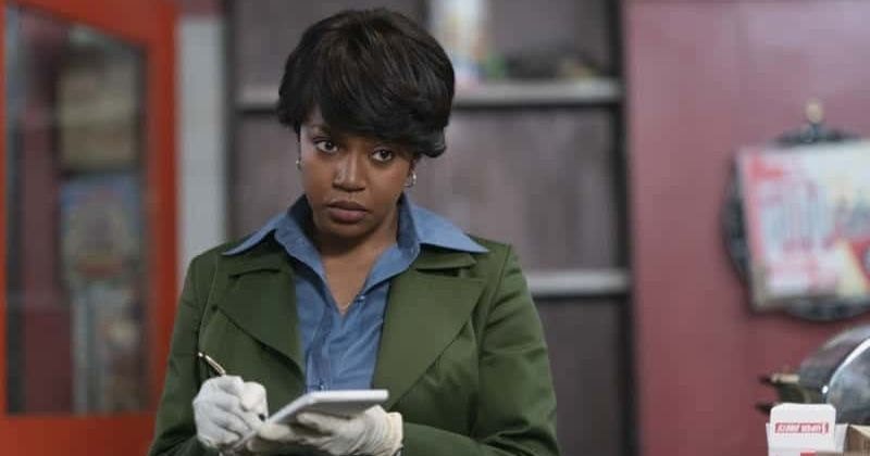 Image: Millie, an FBI agent, is a Black woman with short dark hair, wearing a blue button-up shirt and a green trenchcoat, visible from mid-torso up. She is wearing white latex gloves and writing in a notebook with a skeptical facial expression.
