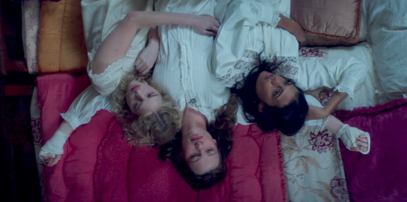 Image: View from above of three women lying on what seems to be a pile of differently-colored blankets: dark pink, flowered, gold and white. The three girls are all wearing white nightgowns and tangled up in each other. One is white with blonde curly hair, the girl in the middle is white with brown hair, the girl on the other side is brown with dark hair. The pose is upside-down. It is hard to tell what they are thinking.
