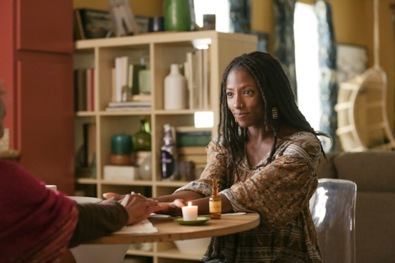 Image: Nova, played by Rutina Wesley, a Black woman in dreadlocks wearing a flowy shirt, is holding someone's hands while sitting at a table that has a little candle on it.