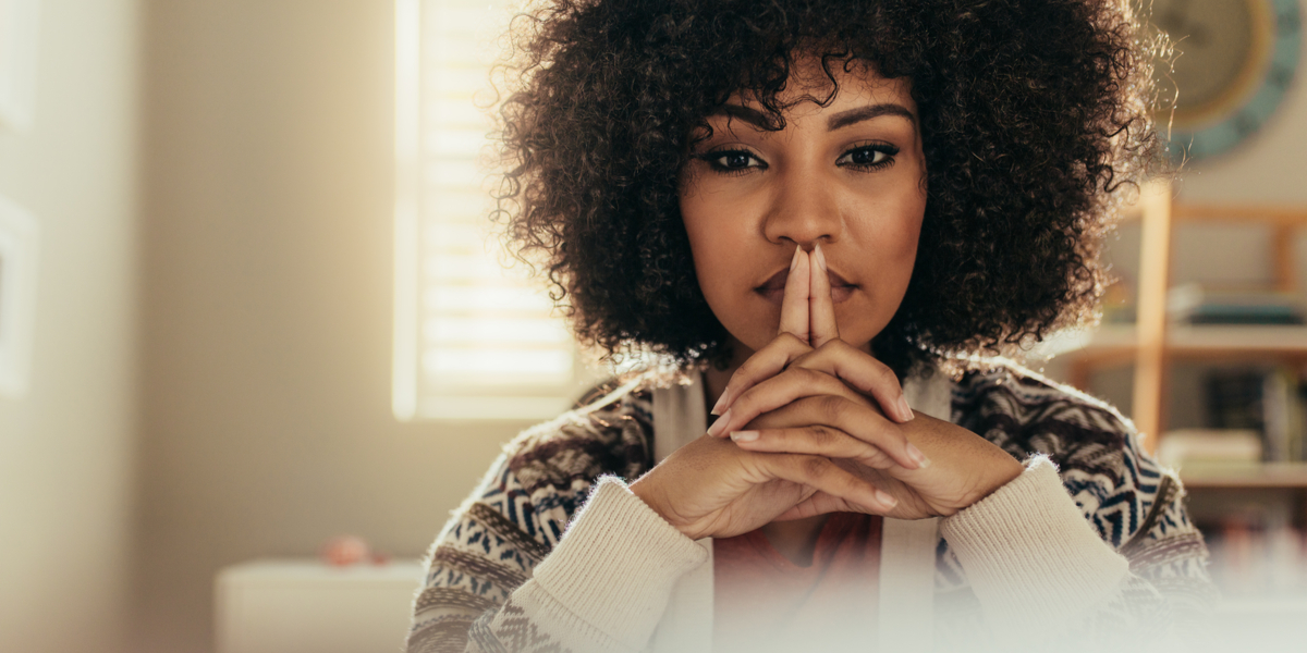 A Black woman with natural hair and a warm, serious expression wearing a patterned knit sweater looks directly at the camera, hands clasped in front of her chin and forefingers steepled together in front of her mouth.