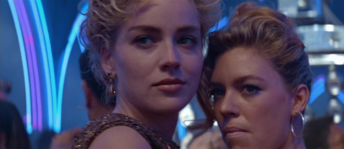 Two women with serious early 90s hair in a dance club, looking at someone with scheming facial expressions