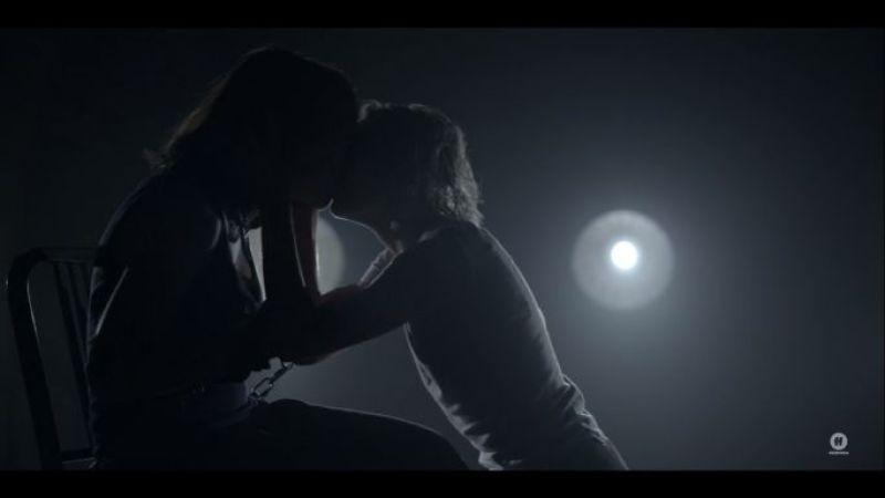 Raelle kisses Scylla in the backlit cell