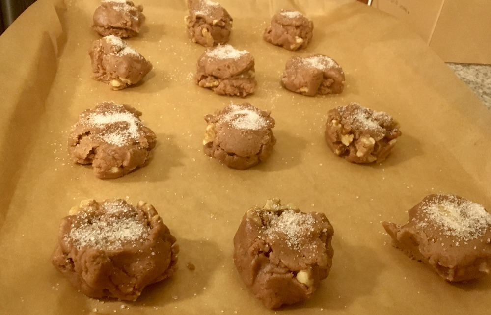 cookie dough balls lined up on a baking sheet with sugar on top