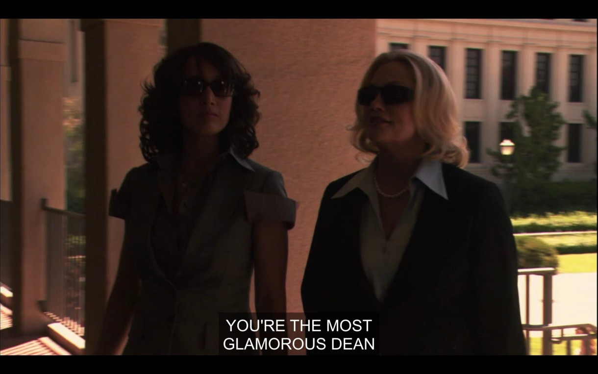 """Bette and Phyllis, both wearing dark sunglasses, are walking into a building from outside. Phyllis says, """"You're the most glamorous dean."""""""