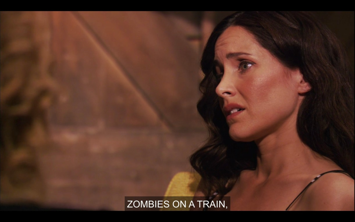 """Helena sits in a yellow chair, looking disappointed after getting fired. Tina, who is off screen, says """"Zombies on a Train."""""""