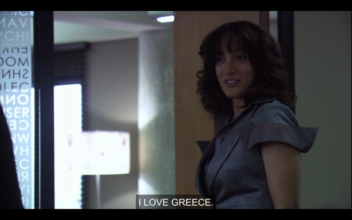 """Bette stands in the doorway of her office. She says to one of her TAs (who is off screen), """"I love Greece."""""""