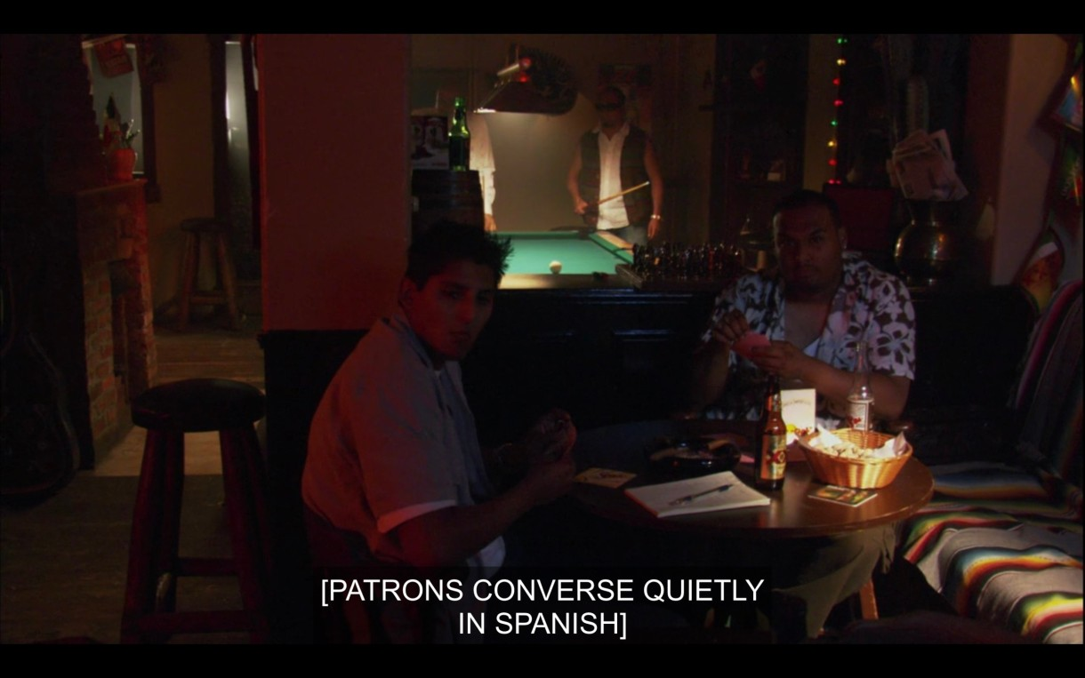 """A dimly lit bar with a pool table in the background and two guys sitting at a table. Subtitles read, """"[Patrons converse quietly in Spanish.]"""""""