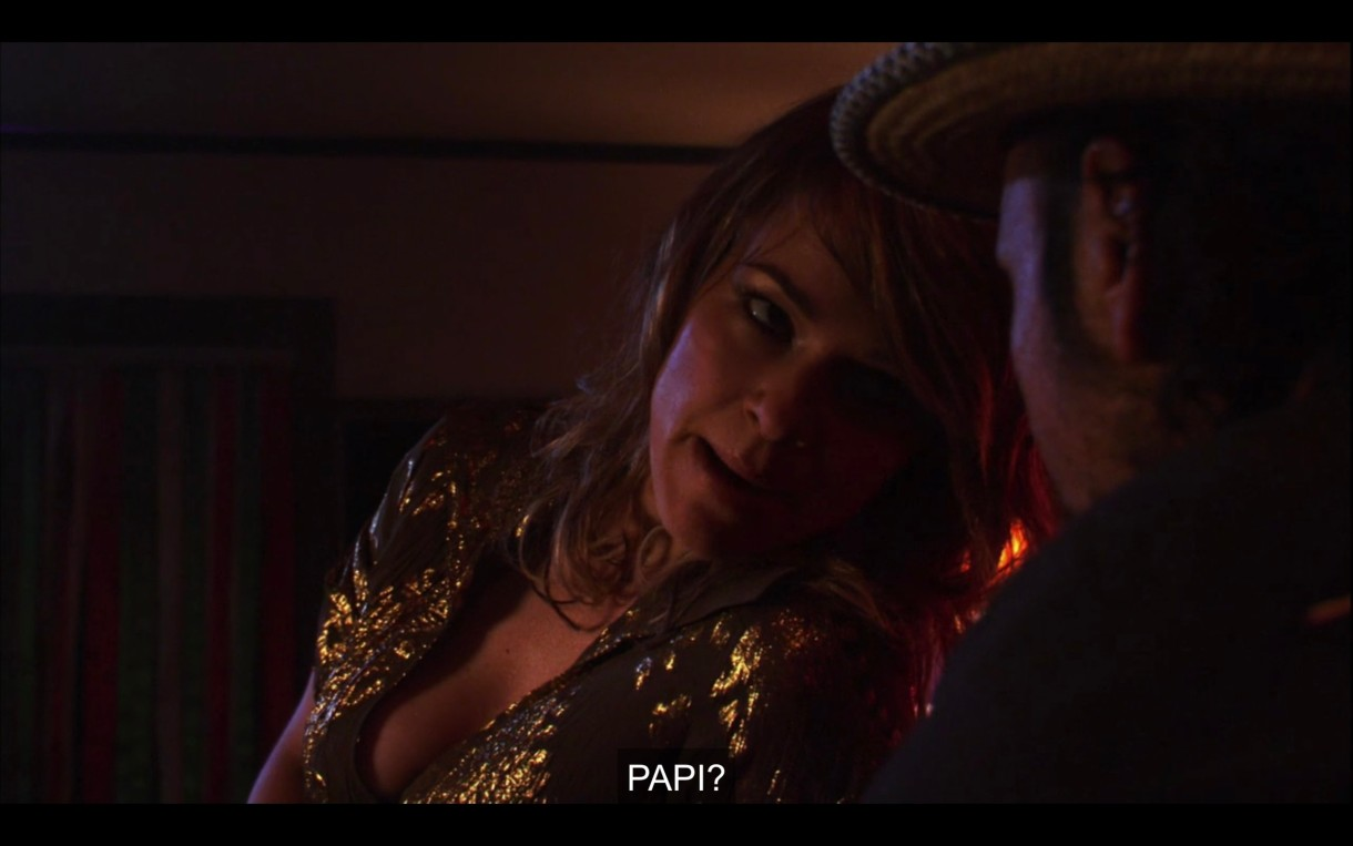 """Alice is wearing a gold sparkly top and leans over to a patron at the bra. She asks, """"Papi?"""""""