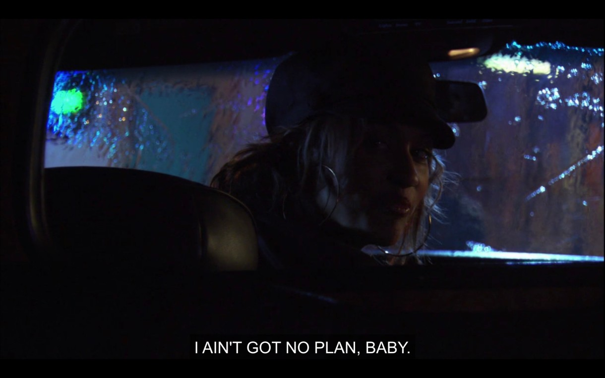 """Papi is driving a car and looks into the backseat. She says, """"I ain't got no plan, baby."""""""