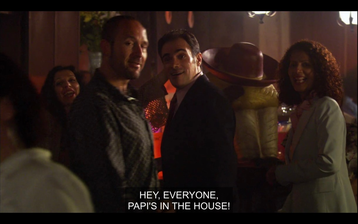 """A crowd of unknown people at a bar. One of them shouts, """"Hey, everyone, Papi's in the house!"""""""