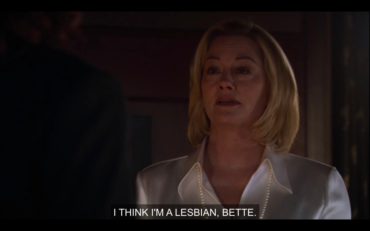 """Phyllis is wearing a white silk blouse and a long strand of pearls. She says, """"I think I'm a lesbian, Bette."""""""