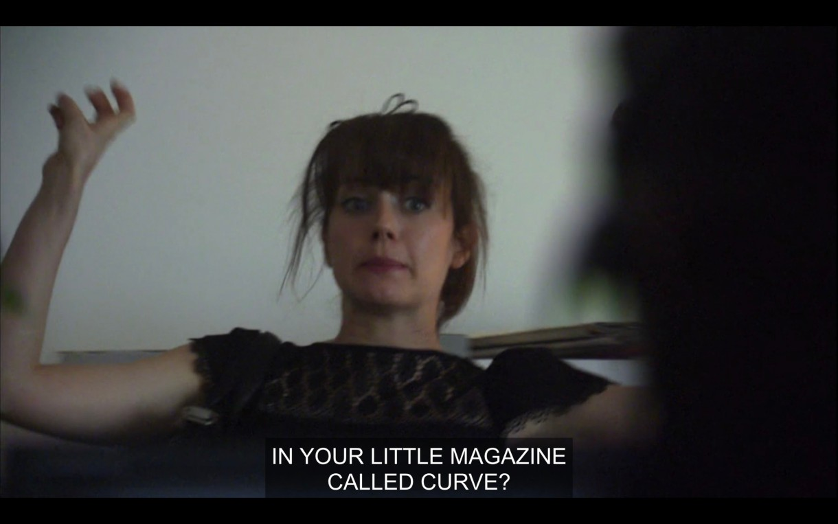 """Jenny is sitting back in a chair with her arms in the air. She says, """"In your little magazine called Curve?"""""""