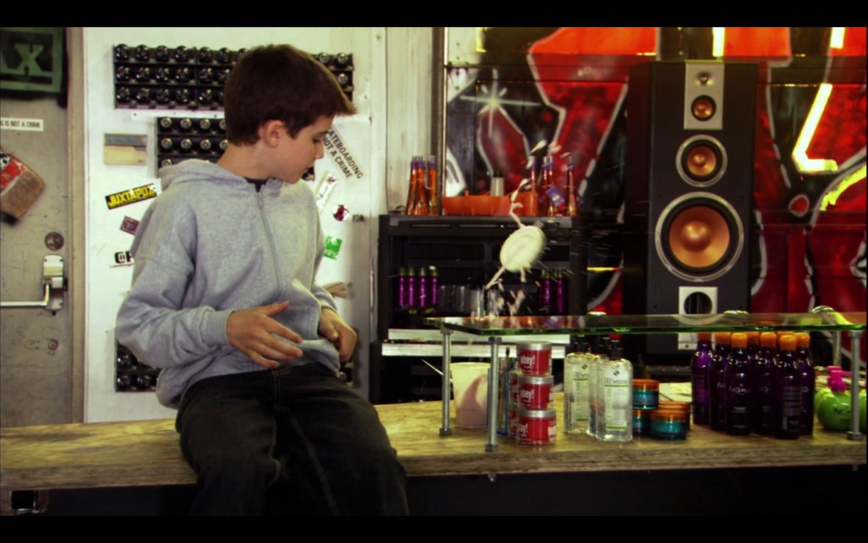 Shay sits on the counter at the skate shop, wearing a grey hoodie. He's looking at the haircare products on display.