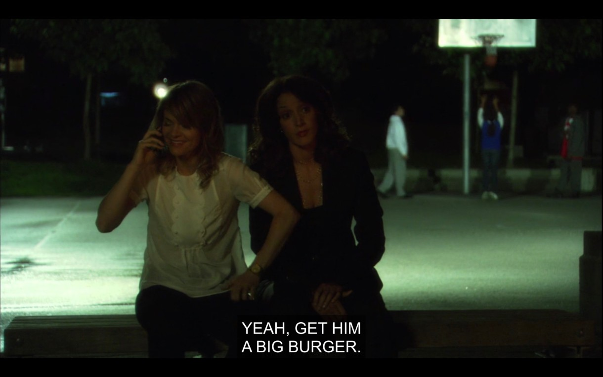 """Alice and Bette sit on a bench near a basketball court. Alice is talking to Shane on the phone. Alice says, """"Yeah, get him a big burger."""""""