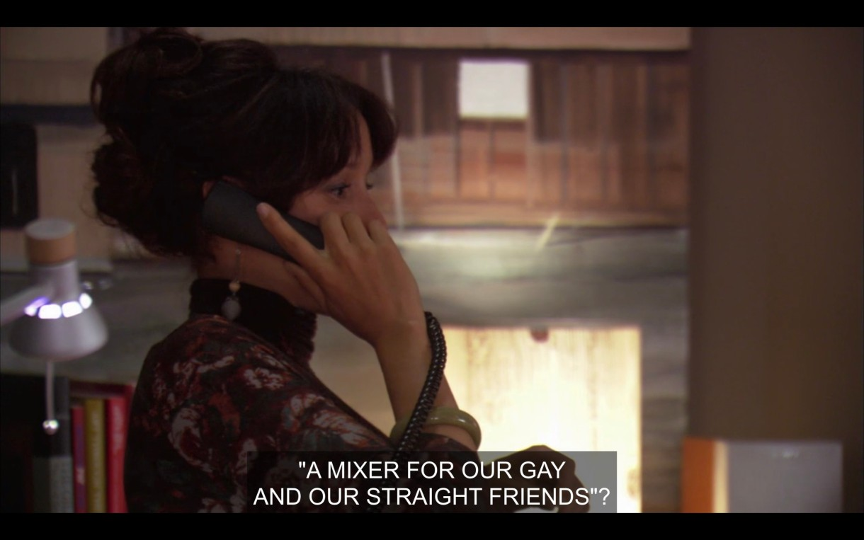 "Bette's talking on the phone in her office. She asks, ""A mixer for our gay and our straight friends?"""