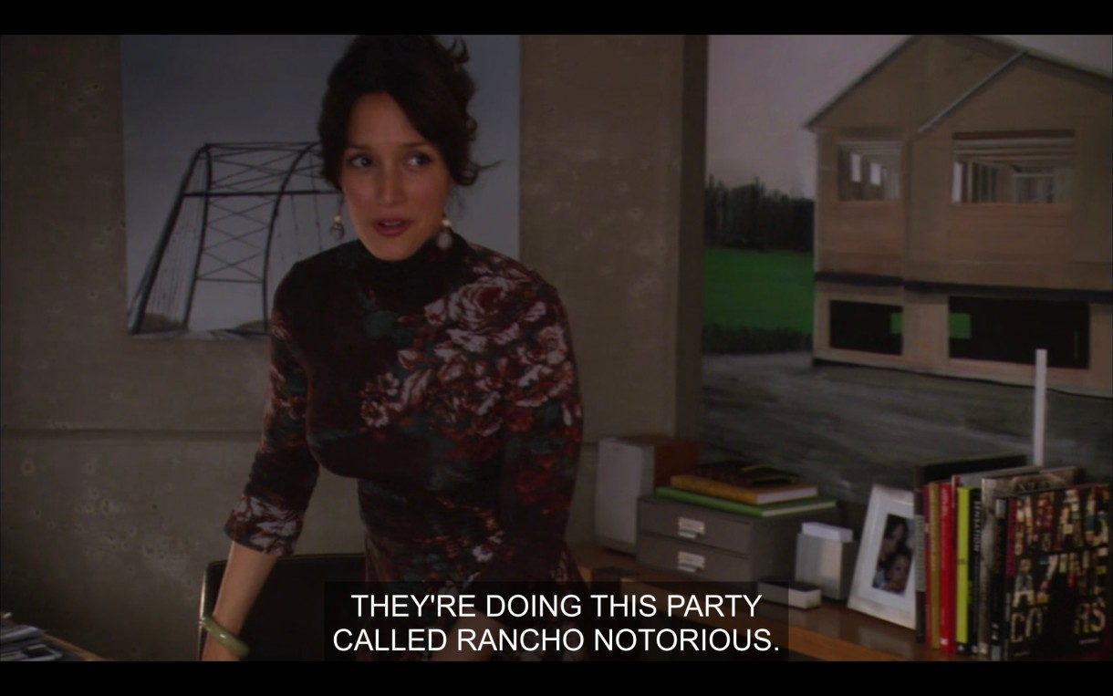 "Bette leans on her desk in her office. She says, ""They're doing this party called Rancho Notorious."""