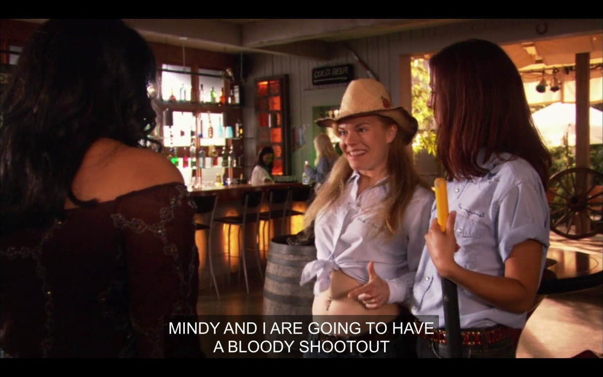 "Two waitresses at the Planet, one wearing a cowboy hat, the other holding a broom. One of them says, ""Mindy and I are going to have a bloody shootout."""
