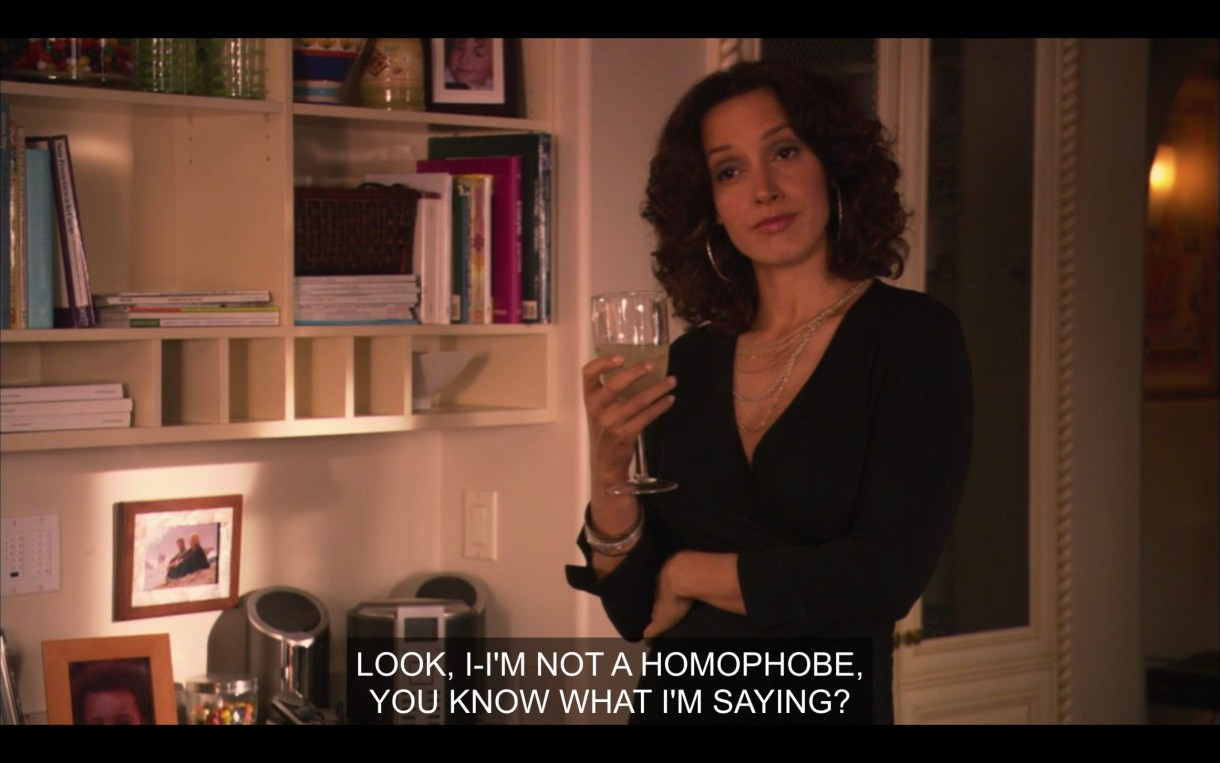 "Bette stands with a wine glass in her hand as a straight cis partygoer, off camera, says, ""Look, I-I'm not a homophobe, you know what I'm saying?"" She has a ""what in the actual fuck?"" look on her face."