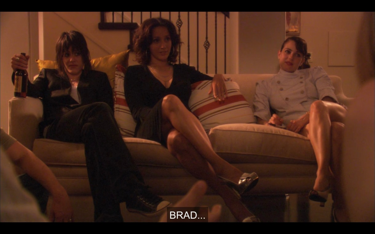 Shane, Bette, and Jenny sit on a couch at Tina and Henry's party, looking bored and annoyed by straight people.