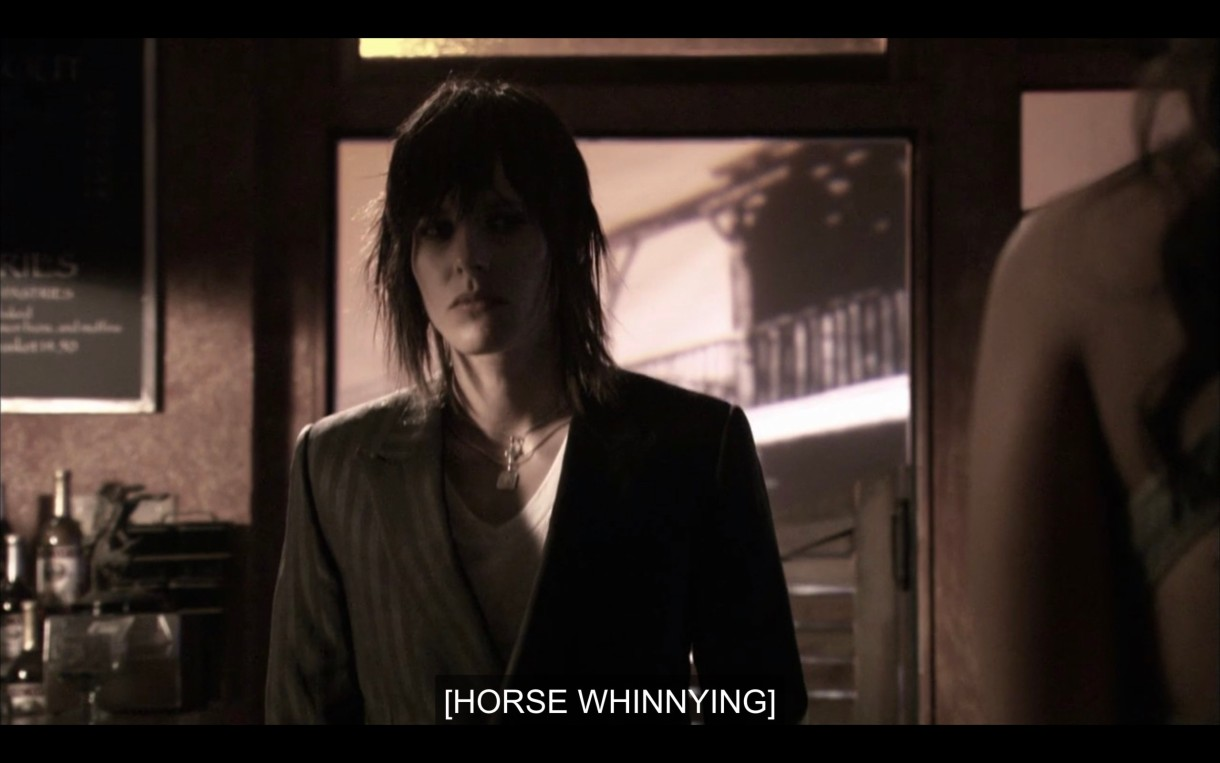 "Black and white shot. Shane walks into The Planet. Subtitles read ""[horse whinnying]"""