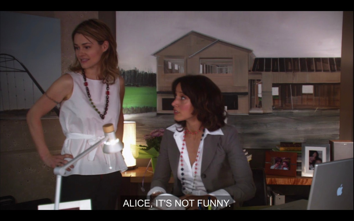"Alice stands next to Bette, who is sitting at her desk in her office. Bette says, ""Alice, it's not funny,"" referring to Phyllis' crush on Alice."