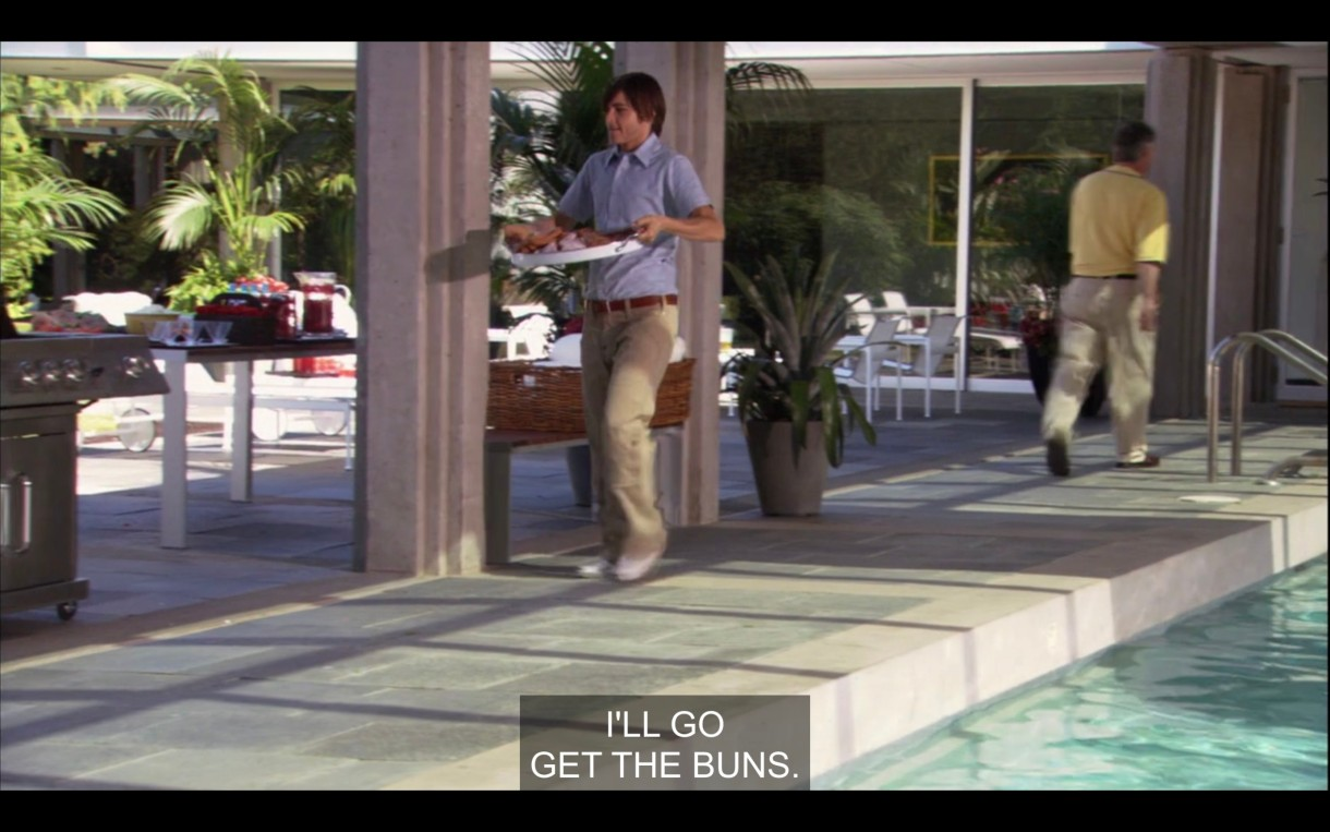 "Max carries a platter of burgers to the grill at his boss's house. His boss says, ""I'll go get the buns"" as he walks away."