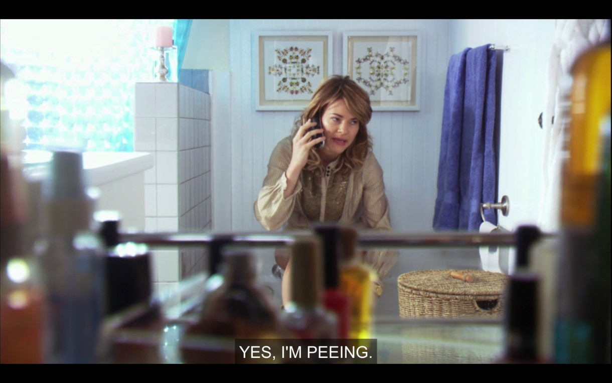 "Alice is wearing a brown top and sitting on the toilet, talking on her cell phone. She says, ""Yes, I'm peeing."""
