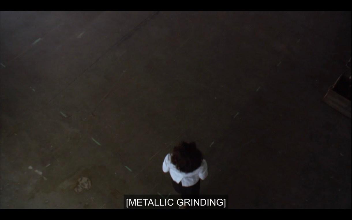 "Overhead shot of Bette standing on a dark concrete floor as she enters Jodi's studio. Subtitles read, ""[Metallic grinding]"""