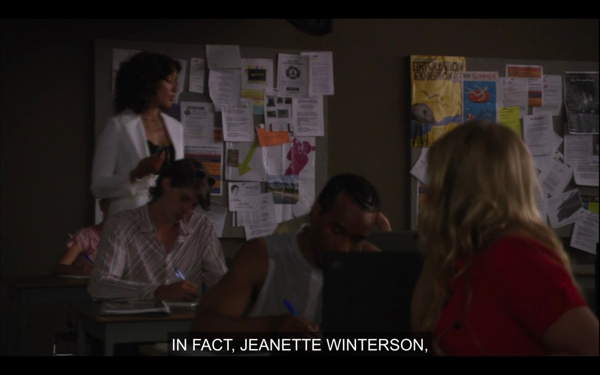 "Bette is wearing a bright white blazer and pacing around the classroom giving a lecture. She says, ""In fact, Jeanette Winterson..."""