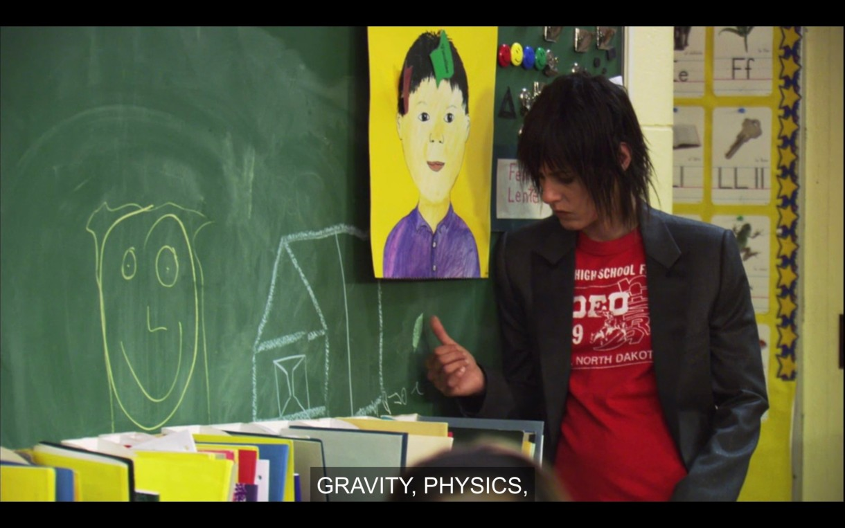 Shane (wearing a red t-shirt under a black blazer) leans against a green chalkboard in Shay's classroom. There is a smiley face and a house drawn on it.