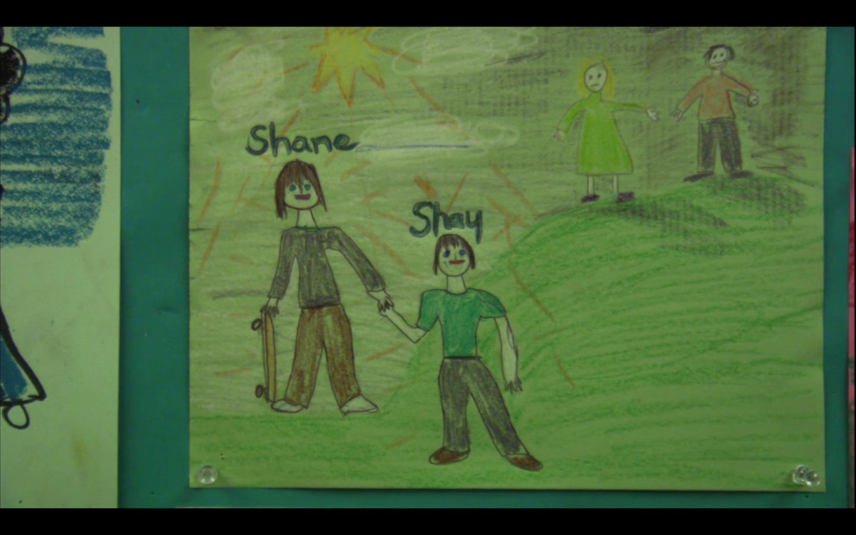 A drawing that Shay drew of his family. In the picture, Shane has a skateboard and is holding hands with Shay. Off in the corner are Shay's mom and dad.