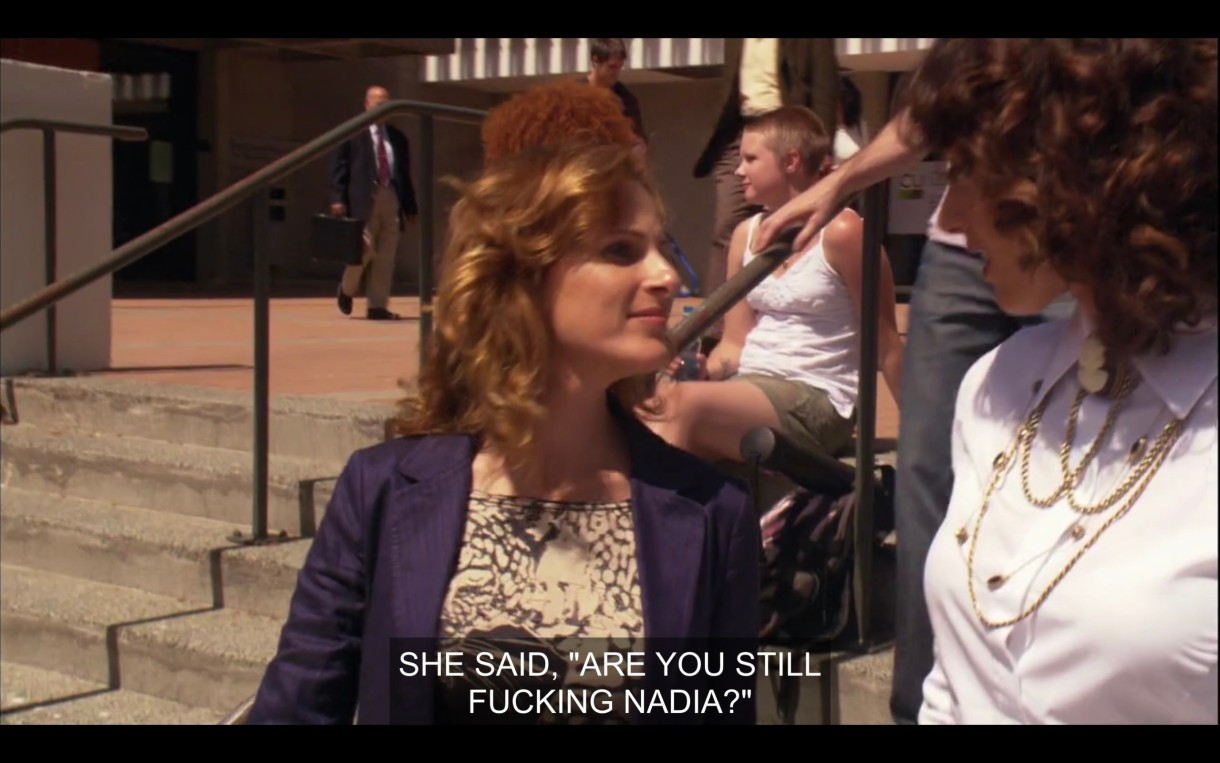 """Jodi (in a blue blazer) and Bette (in a white blouse with a gold necklace) standing outside on concrete steps. """"She said, 'Are you still fucking Nadia?'"""""""