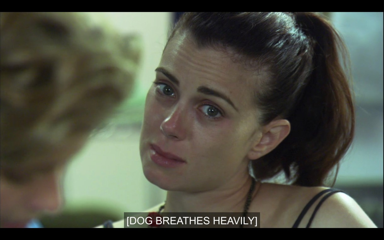 """Close-up of Jenny with tears in her eyes. She's wearing a black tank top and her hair in a ponytail. Subtitles read, """"[Dog breathes heavily]"""""""