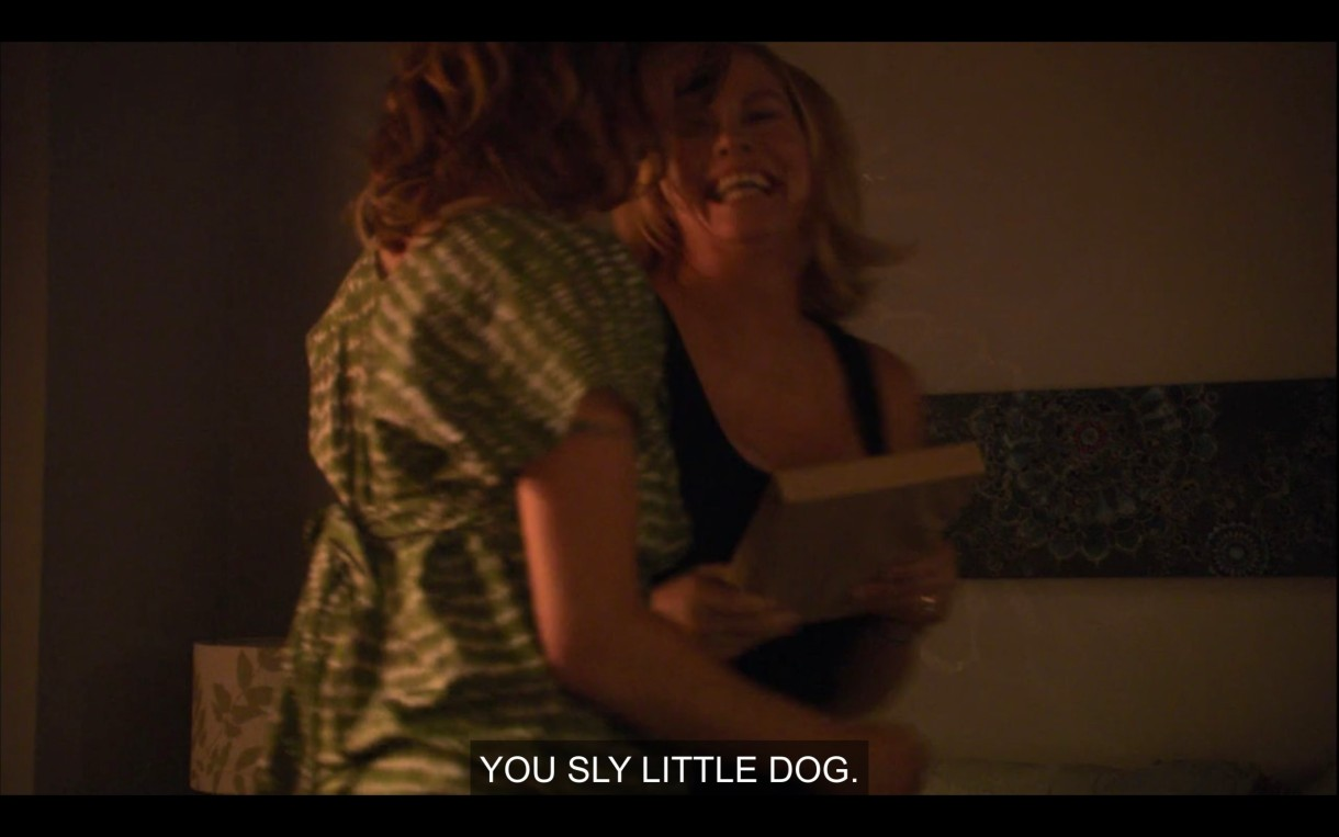 """Phyllis and Alice in a dimly-lit room. Phyllis has a book in her hands. Alice says, """"You sly little dog."""""""