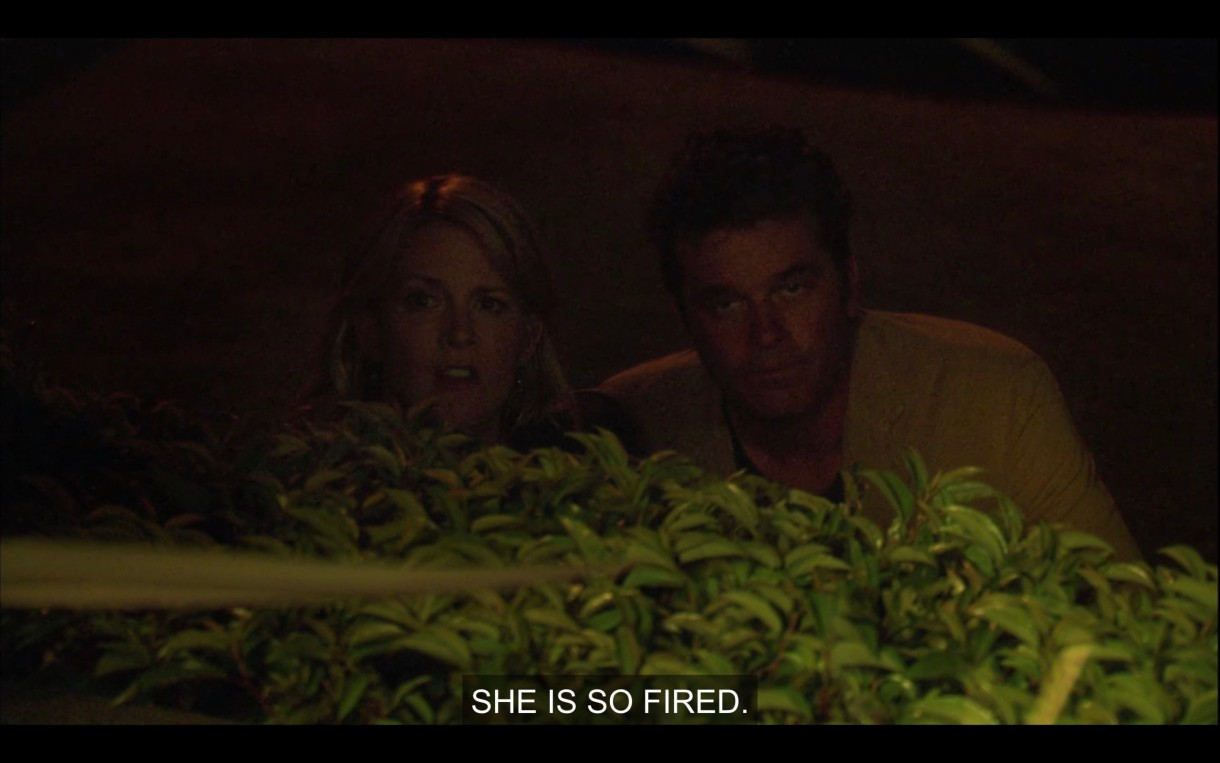 """Tina and Henry hiding behind a bush in the dark. Tina says, """"She is so fired."""""""