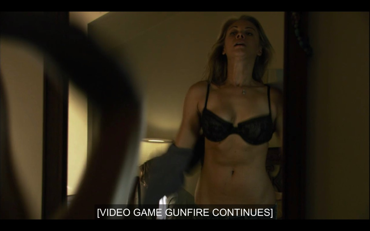 """Paige in a black bra standing in front of a mirror. Subtitles read, """"[Video game gunfire continues]"""""""