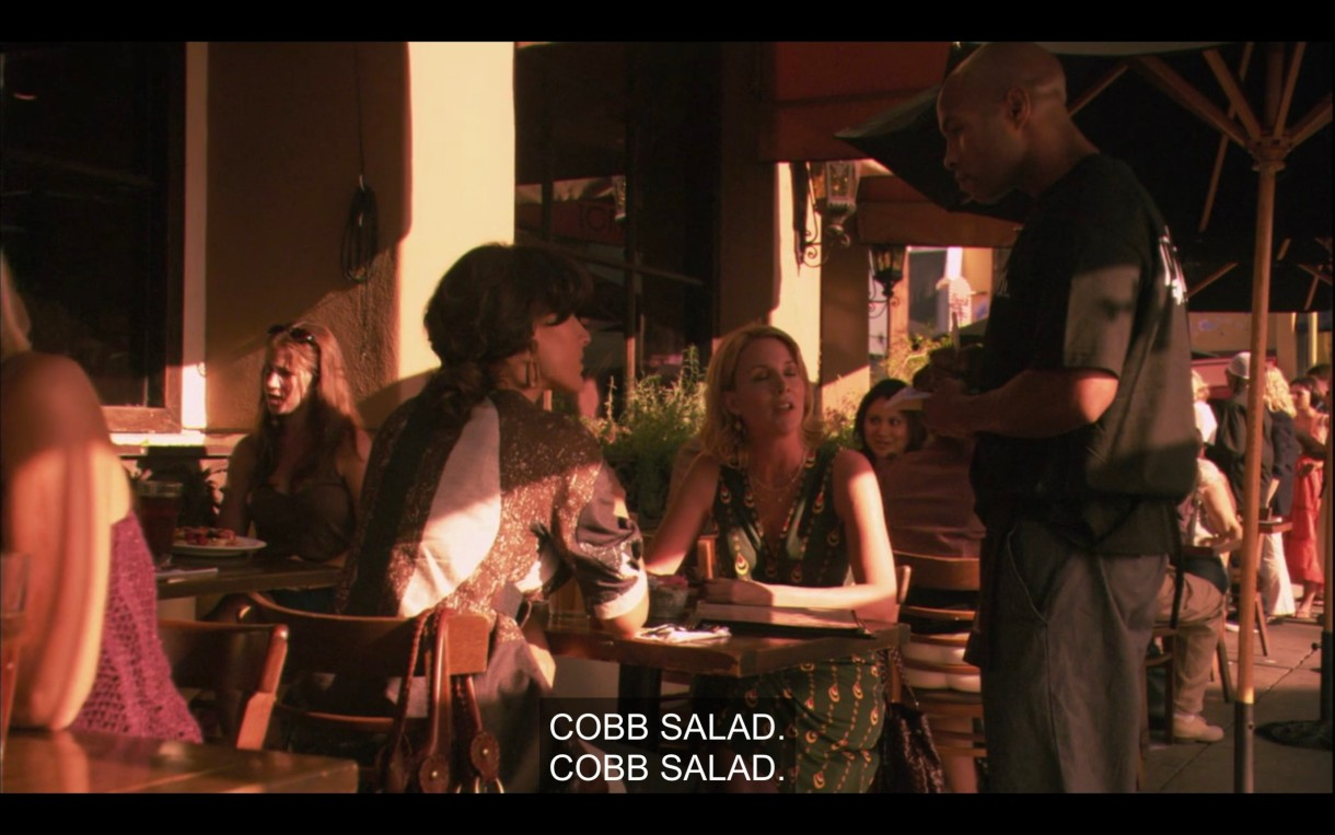 Tina and Bette sit at an outdoor restaurant table. They both order a Cobb salad from the waiter standing next to them.