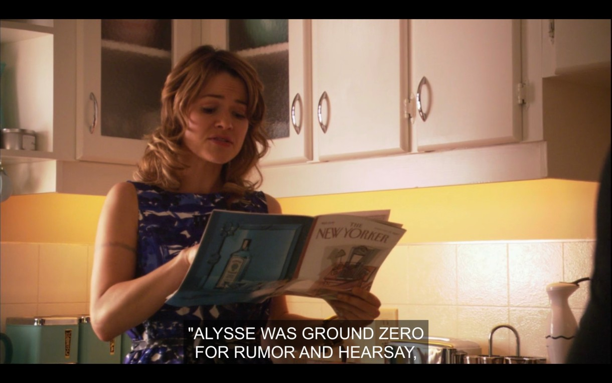 """Alice (wearing a blue dress) stands in the kitchen holding The New Yorker magazine. She reads, """"Alyssa was ground zero for rumor and hearsay."""""""