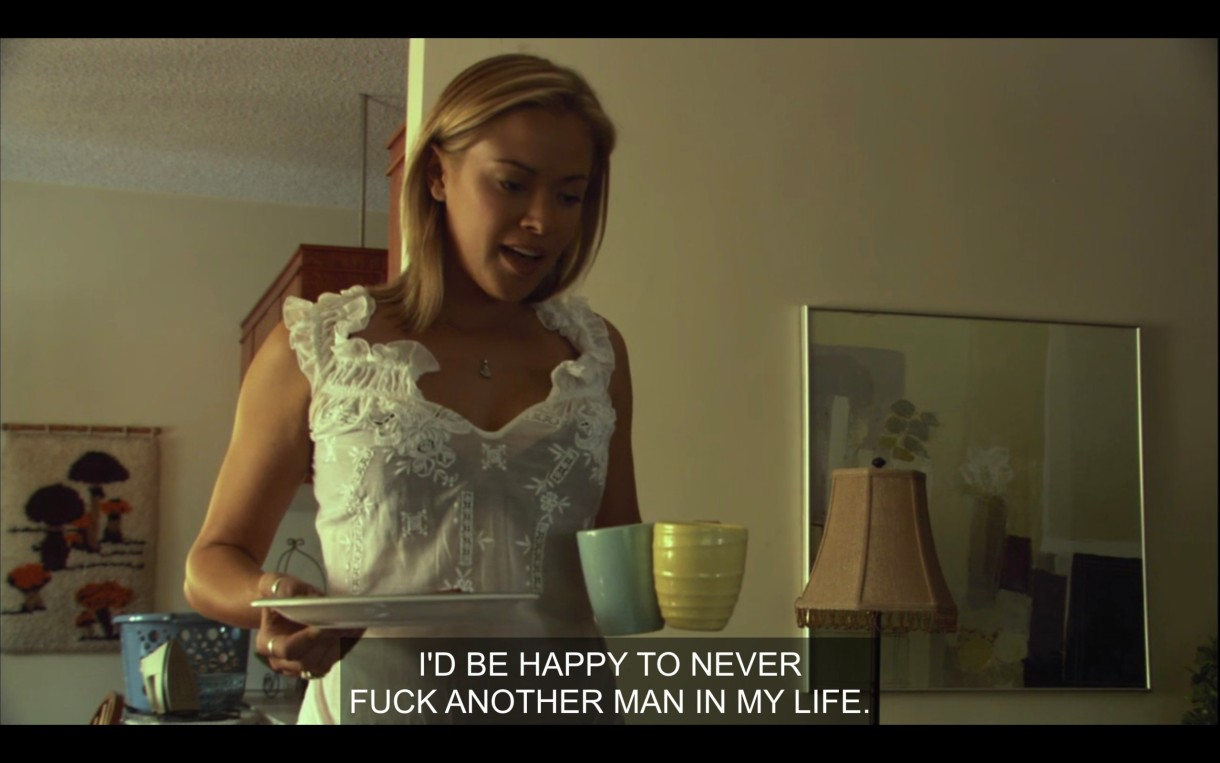"""Paige (wearing a white blouse) holds a plate and two coffee mugs in her hands. She says, """"I'd be happy to never fuck another man in my life."""""""