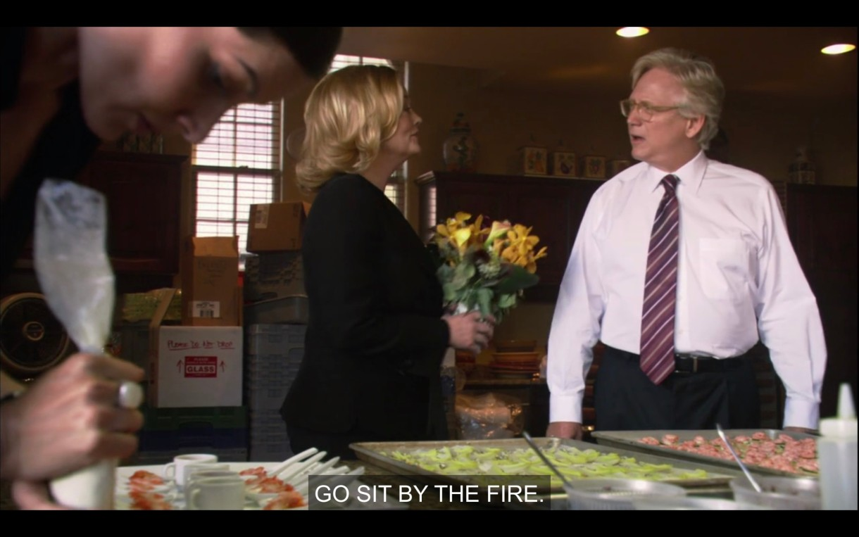 """Phyllis (in a black blazer) stands in a commercial kitchen, telling an old white guy in a white shirt and red tie, """"Go sit by the fire."""""""