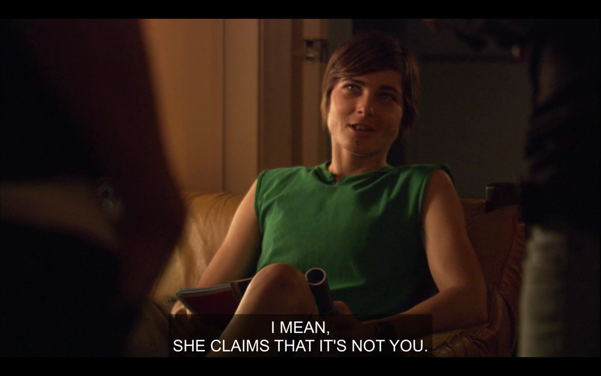 """Max sits on a chair in the living room wearing a green cut-off shirt. He says, """"I mean, she claims that it's not you."""""""