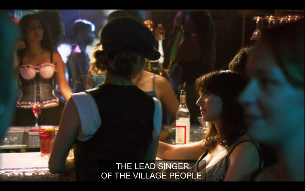 """Alice and Jenny stand in a crowded bar. Jenny says, """"The lead singer of the village people."""""""